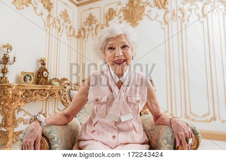 Joyful mature lady is relaxing on classy furniture and smiling. She is looking at camera with happiness