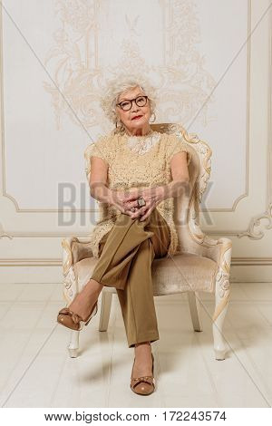 Smart old woman is sitting on luxury chair and looking at interlocutor with seriousness