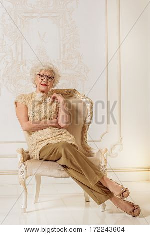 Elegant senior lady is listening to someone with attention. She is sitting on confortable armchair with relaxation
