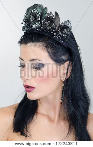 A girl in a black crown looking to the right
