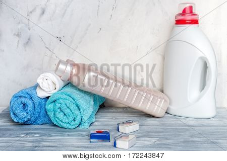 housekeeping set with towels and plastic bottles in laundry on gray desk background mockup