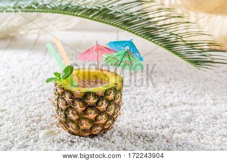 Tropical Drink In Pineapple With Cocktail Umbrellas