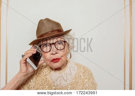 Who is this. Surprised old woman is answering the phone. She is standing and staring at camera with shock