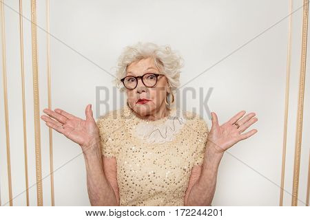 I do not know. Confused old woman is standing and gesturing with misunderstanding