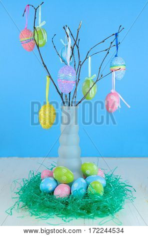An Easter Tree of sparkly colorful eggs hanging from small tree branches in a tall vase. More eggs around the base in green Easter grass. Wood table with blue background
