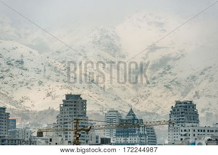 Severe snowy mountains are close to new modern buildings