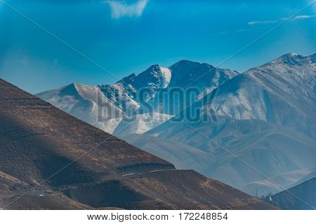 Magnificent mountains are rising up to blue clear sky and bright sun