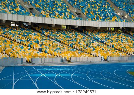 Empty colorful stadium seats and running tracks