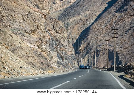 Highway with electrical wires is among high rocky hills