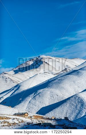 Great mountains are covered with sparkling cold snow. Lonely house is in foothill