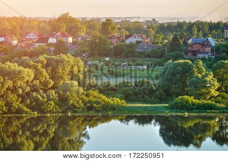 Spring landscape - countryside in the spring forest near the river in early spring morning.  Spring landscape of small village in the nice spring morning weather. Natural spring landscape