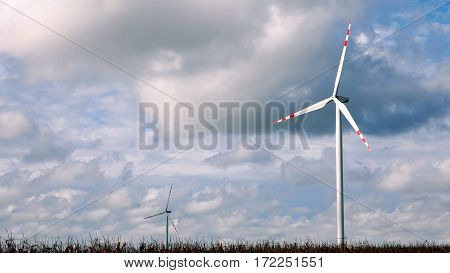 Wind turbines over stormy cloudy sky using renewable energy to generate electrical power. Renewable energy is most environmental way of power generation.