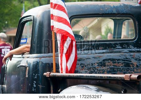 An American flag is attached to the back of an old beat up pickup truck driving in an Independence Day Parade.