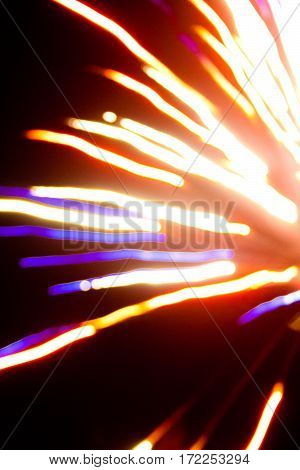 Abstract blur of a colorful firework against a black sky.