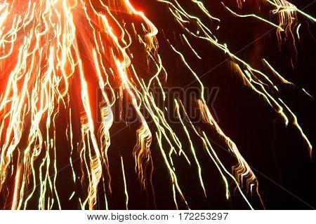 An abstract blur of a firework against a black sky.