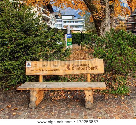 Engelberg, Switzerland - 12 October, 2015: bench on the square at the office of the Obwalden Cantonal Bank with promotion on it. Obwalden Cantonal Bank (German: Obwaldner Kantonalbank) is the cantonal bank of the Swiss canton of Obwalden.