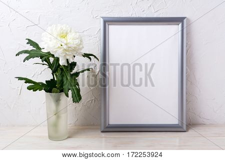 Silver frame mockup with white chrysanthemum in glass vase. Empty frame mock up for presentation design.