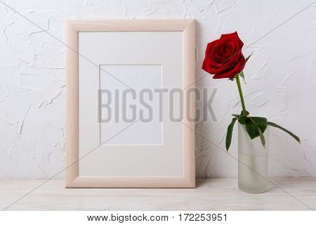 Wooden frame mockup with red rose in glass vase. Empty frame mock up for presentation design.