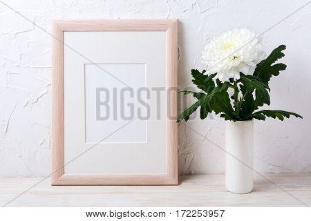 Wooden frame mockup with white chrysanthemum in vase. Empty frame mock up for presentation design.