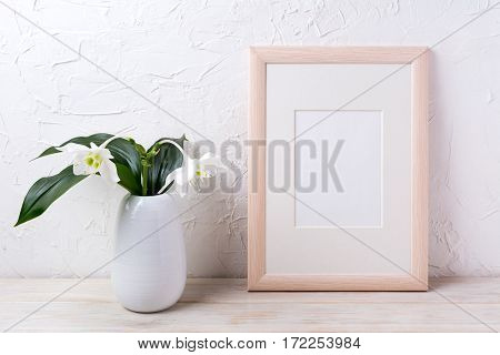 Wooden frame mockup with tender white lily in vase. Empty frame mock up for presentation design.