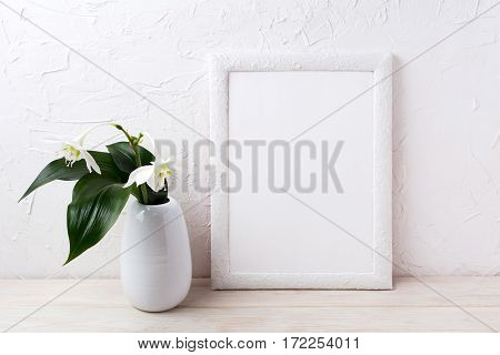 White frame mockup with euxaris flower in vase. Empty frame mock up for presentation artwork.