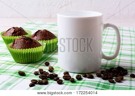 White mug mockup with chocolate muffins on green checkered napkin. Empty mug mock up for design presentation.