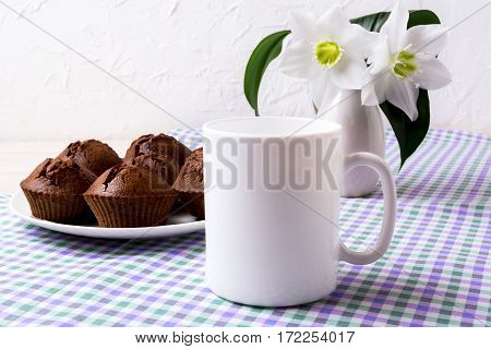 White mug mockup with chocolate muffins on plate. Empty mug mock up for design presentation.