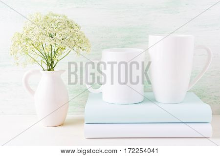 Two white mugs mockup with books and white flowers in pitcher. Empty mug mock up for design presentation.