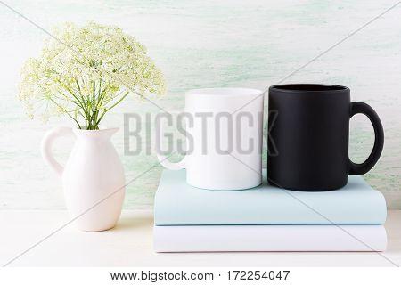 White and black mug mockup with books and white flowers. Empty mug mock up for design promotion.