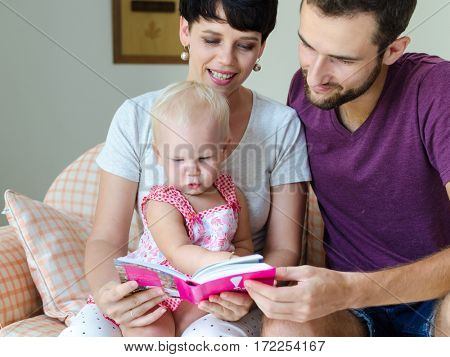Mother, father and daughter reading a book. Family sitting on the couch.