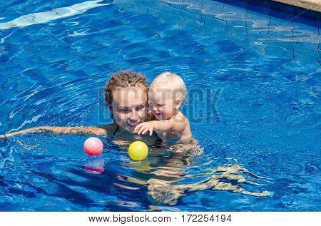 Mother and her child in the pool. Woman playing with a ball with his little daughter.