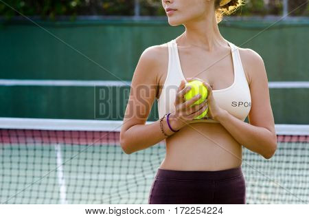 A female holding a bright yellow tennis ball