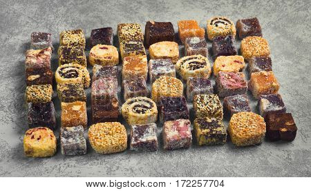 Assorted traditional turkish delight Rahat lokum on gray stone background. Rahat Lukum (lokum) sprinkled with coconut sugar and sesame. Top view from above and copy space.