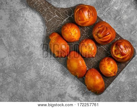 Assortment fresh patties bread buns in wooden board on gray concrete background. Fresh patties bread bun round and oval-shaped with stuffing. Top view from above and copy space.