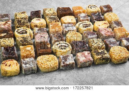 Assorted traditional turkish delight Rahat lokum on gray stone background. Rahat Lukum (lokum) sprinkled with coconut sugar and sesame.