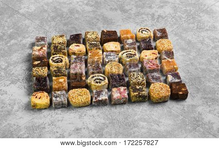 Assorted traditional turkish delight Rahat lokum on gray stone background. Rahat Lukum (lokum) sprinkled with coconut sugar and sesame. poster