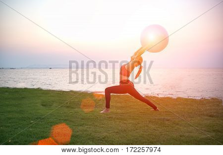 Silhouette yoga ball yong woman in the beach sunset background