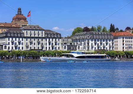 Lucerne, Switzerland - 8 May, 2016: people in boats on Lake Lucerne, buildings on the Schweizerhofquai quay in the background. Lake Lucerne is a lake in central Switzerland, the fourth largest in the country. Lucerne is a city in central Switzerland.
