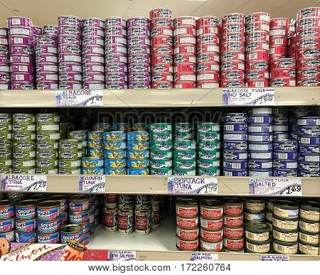 New York Februrary 14 2017: Cans of various types of tuna and other fish are stacked on a shelf in a Trader Joe's store.