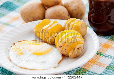 Baked Potatoes And Yellow Eggs On A White Plate