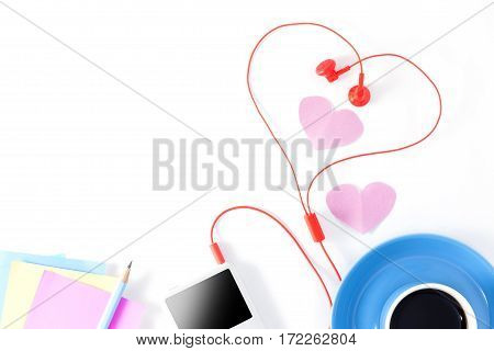Blue coffee cup with music player and red earphone on white backgroundValentine's day concept.