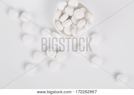 Round white pills and glass of water on a table waiting for eat