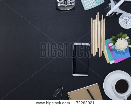 Office black leather desk table with smartphone and office supplies coffee cup Top view with copy space for your text
