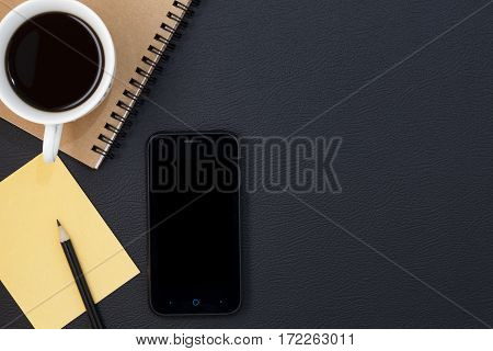 Office black leather desk table with smartphone supplies and coffee cup office accessory Top view with copy space