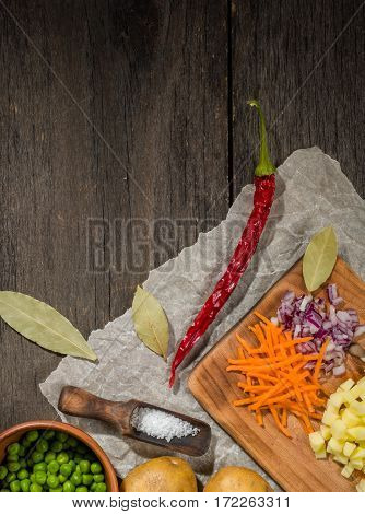 ingredients for vegetable soup. vegetables cucumber onions potatoes carrots peas spices in the section on gray wooden background
