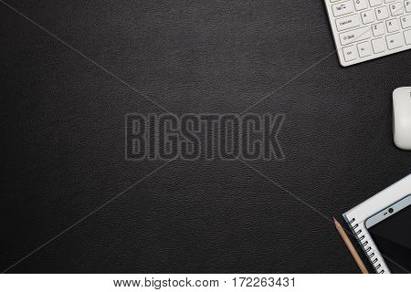 Office black leather desk table with notebookkeyboardmouse. Top view with copy space