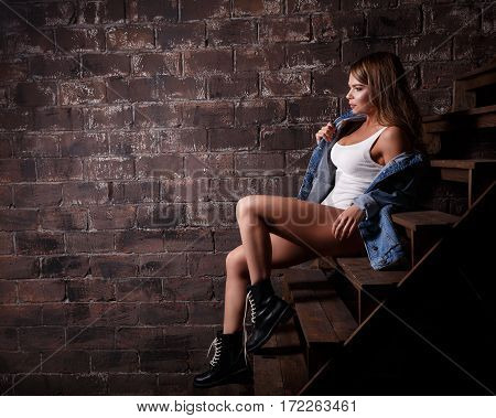Young sexy girl in a denim jacket white T-shirt and high boots sitting on the steps to the loft room.