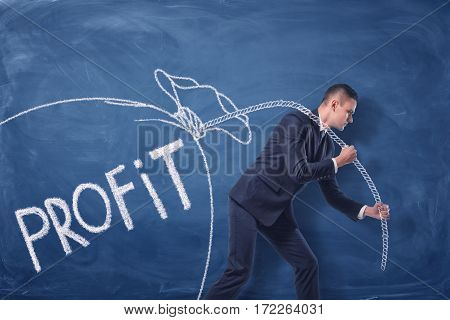 Businessman is pulling a big drawn bag of money on a rope on the blue background. Profit increasing. Business management. Making money