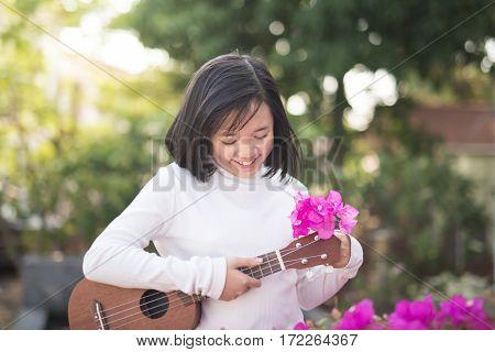 Beautiful asian girl with ukulele Outdoor portrait