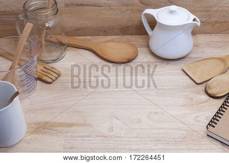measuring cup and wooden spoon cooking supplies on wood background.